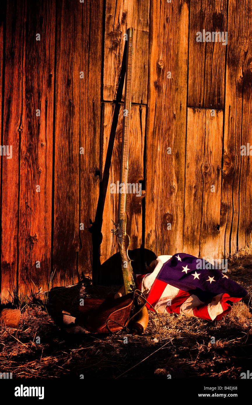 flint lock rifle leaning against barn wall with 13 star colonial United States flag - Stock Image