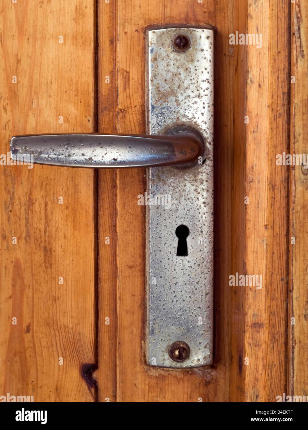 grunge door handle on diry old door - Stock Image