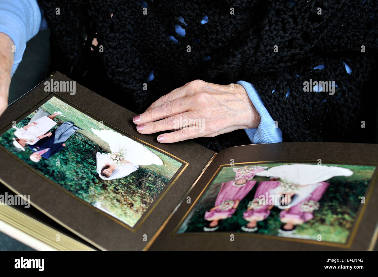 Elderly lady looking at a wedding album and reminiscing - Stock Image