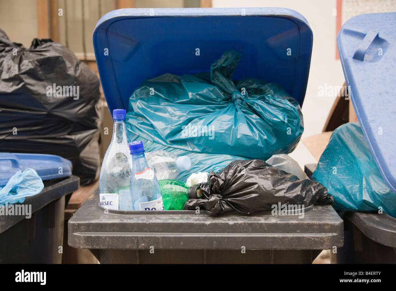 Romania Europe Wheelie bin with lid open overfilled with plastic bags - Stock Image