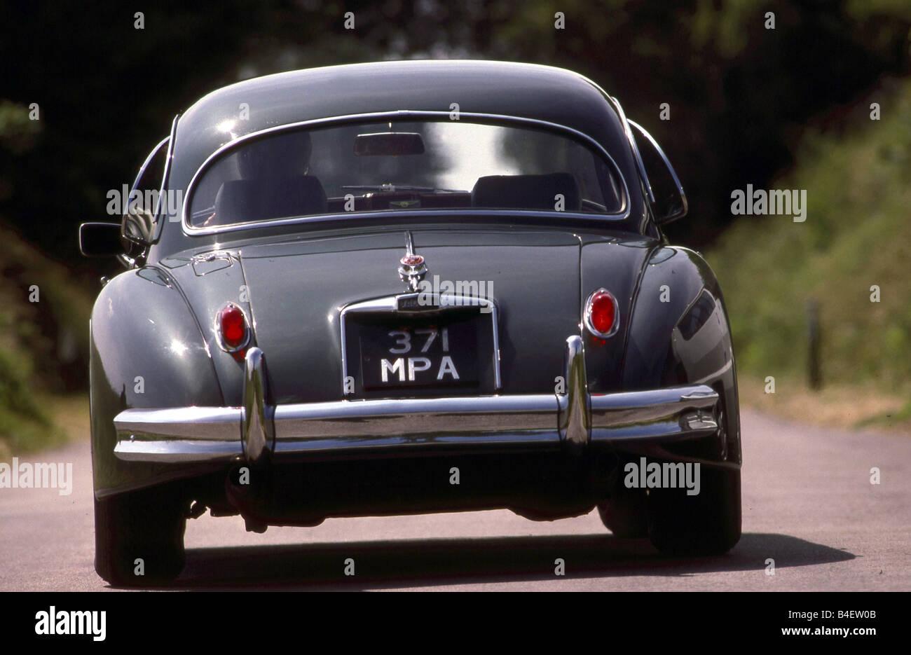 Jaguar XK 150 Coupé, model year 1957-1961, dark grey, standing, back view, road, country road - Stock Image