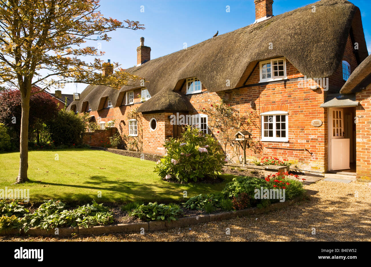 Typical pretty English thatched country cottage or house in the village of All Cannings, Wiltshire, England, Great - Stock Image