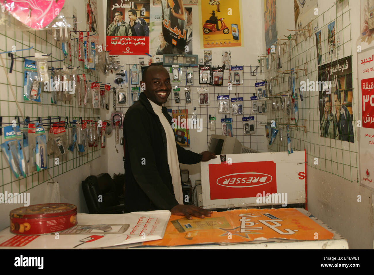 Sudanese Refugee At Mobile Phone Accessories And Repair Shop