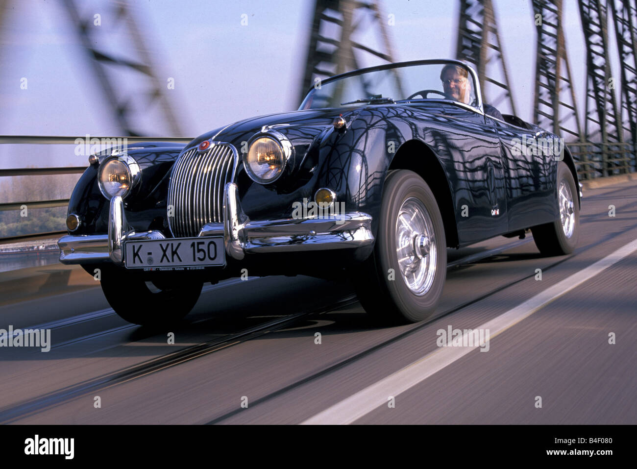Car, Jaguar XK 150, vintage car, black, 1950s, fifties, convertible, convertible top, open,  driving, diagonal front, - Stock Image