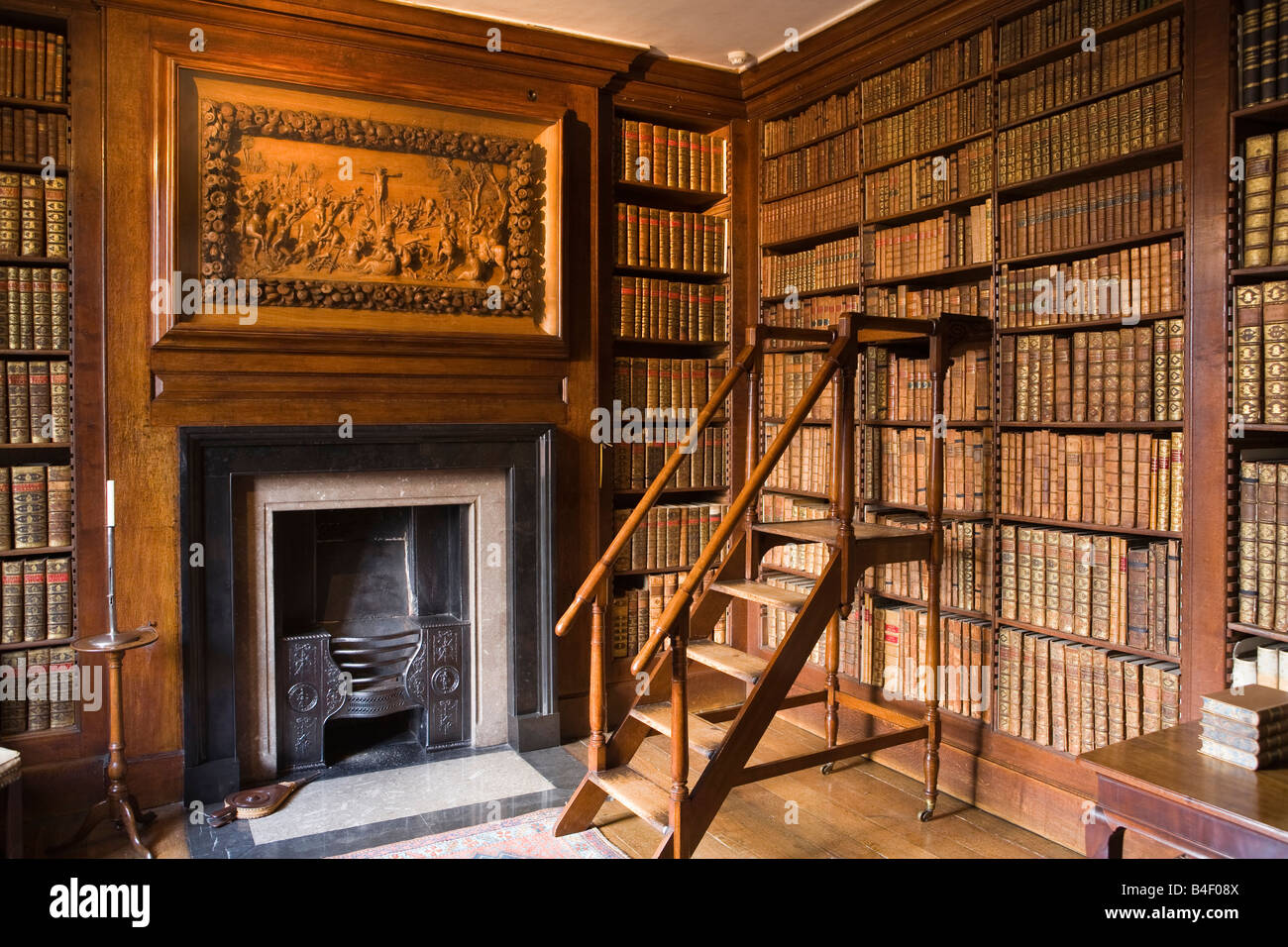 UK Cheshire Altrincham Dunham Massey Hall NT Library Grinling Gibbons crucifixion panel over fireplace - Stock Image