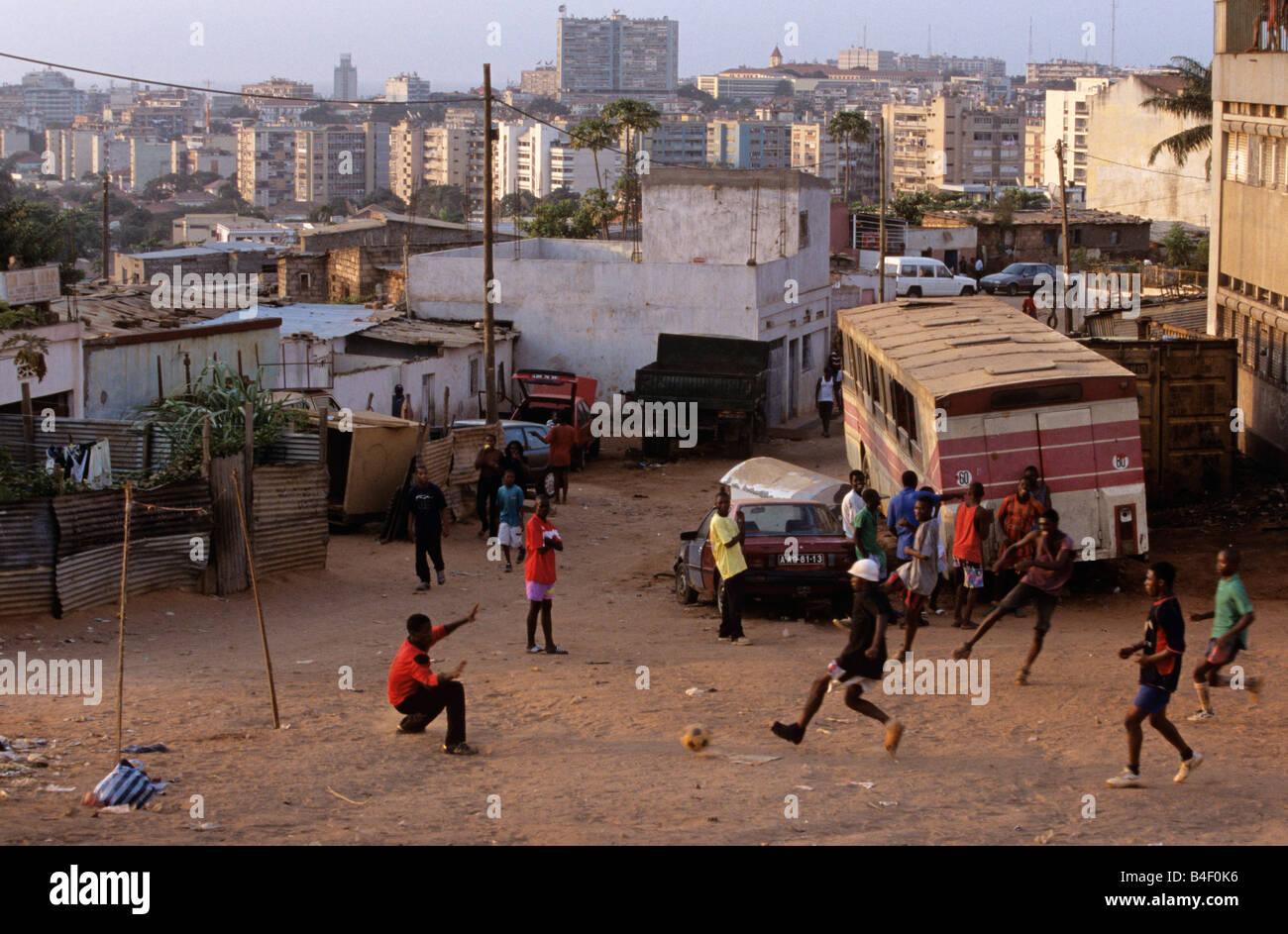 Young men playing football on city wasteland, Luanda, Angola, Africa. - Stock Image