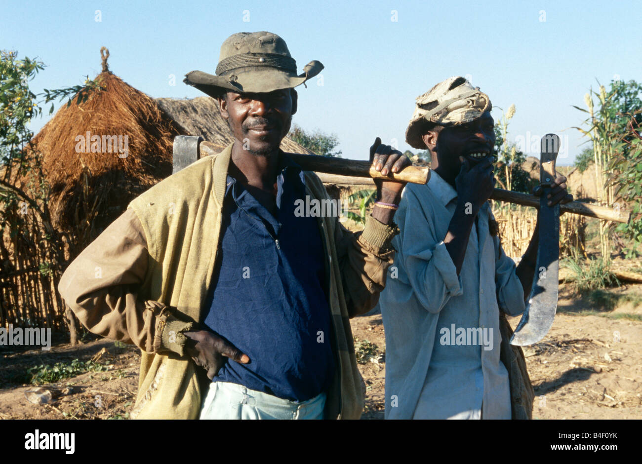 Two male farm workers carrying tools over their shoulders outside mud hut, portrait, Angola, Africa Stock Photo