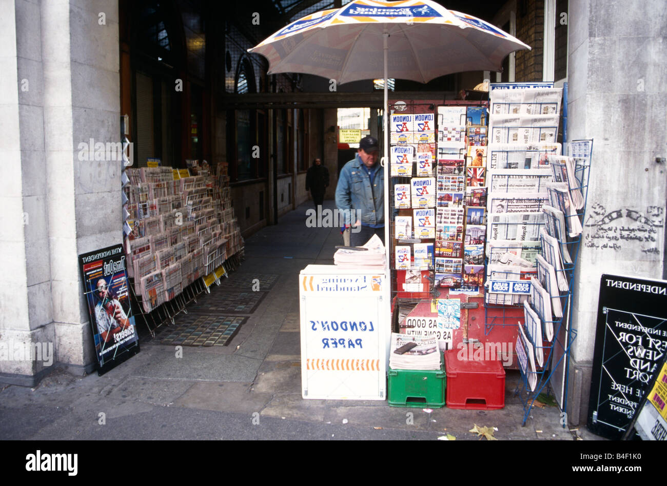 Man at newsstand in walkway, London, England, UK Stock Photo