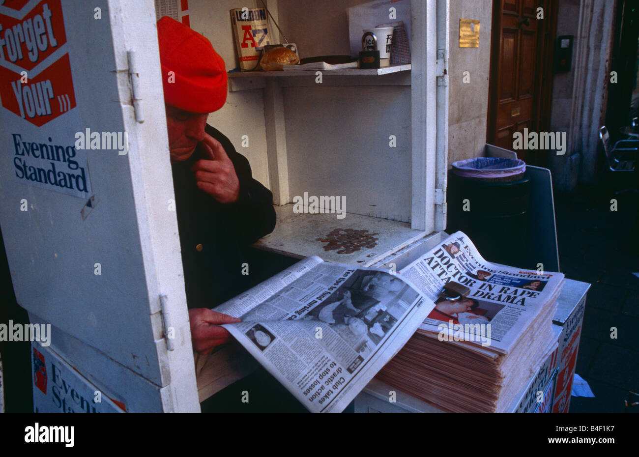 A man reading a newspaper at his stand in London. Stock Photo