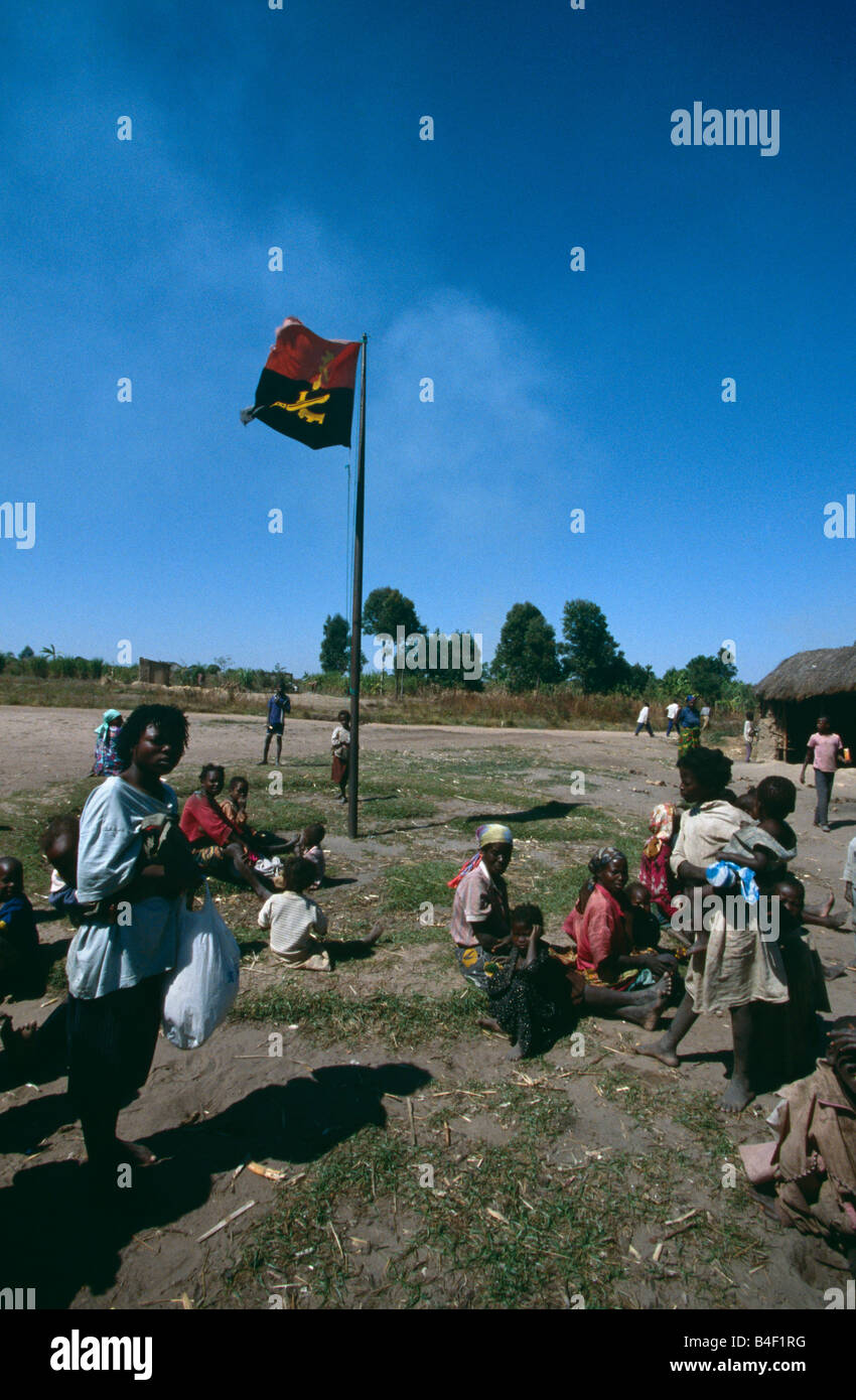 Displaced people sitting around the national flag at a camp in Angola. - Stock Image