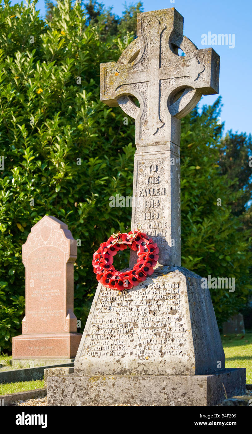 A typical stone war memorial with Celtic cross and poppy wreath taken in the Wiltshire village of All Cannings, - Stock Image