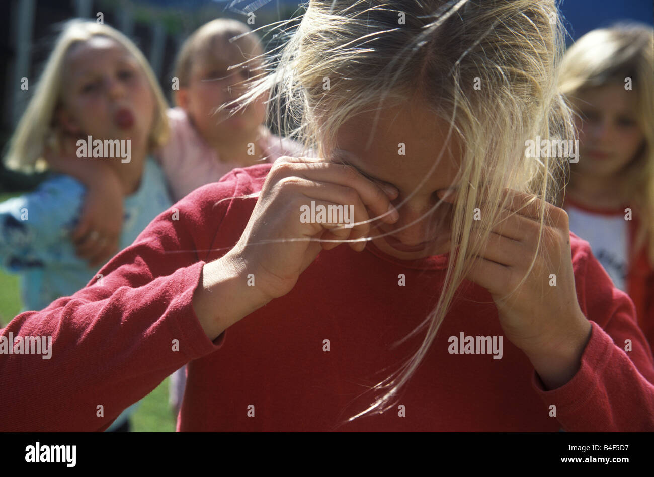 little girl being teased and bullied by other girls Stock Photo