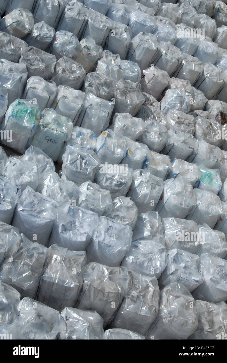 Bales of rigid plastic waste feedstock awaiting reprocessing at a plastics recycling plant - Stock Image