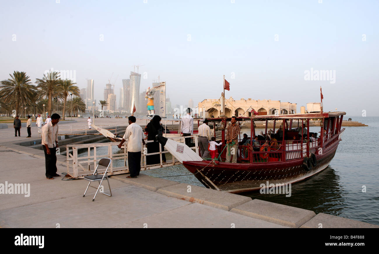 Families boarding a pleasure dhow moored on the Corniche in Doha Qatar The small boats offer pleasure trips around - Stock Image