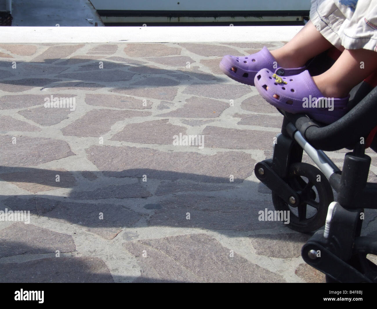 ea251922b437 Kid wearing Crocs shoes. B44WF1 (RM). child wearing crocs type sandals in  pram on street - Stock Image