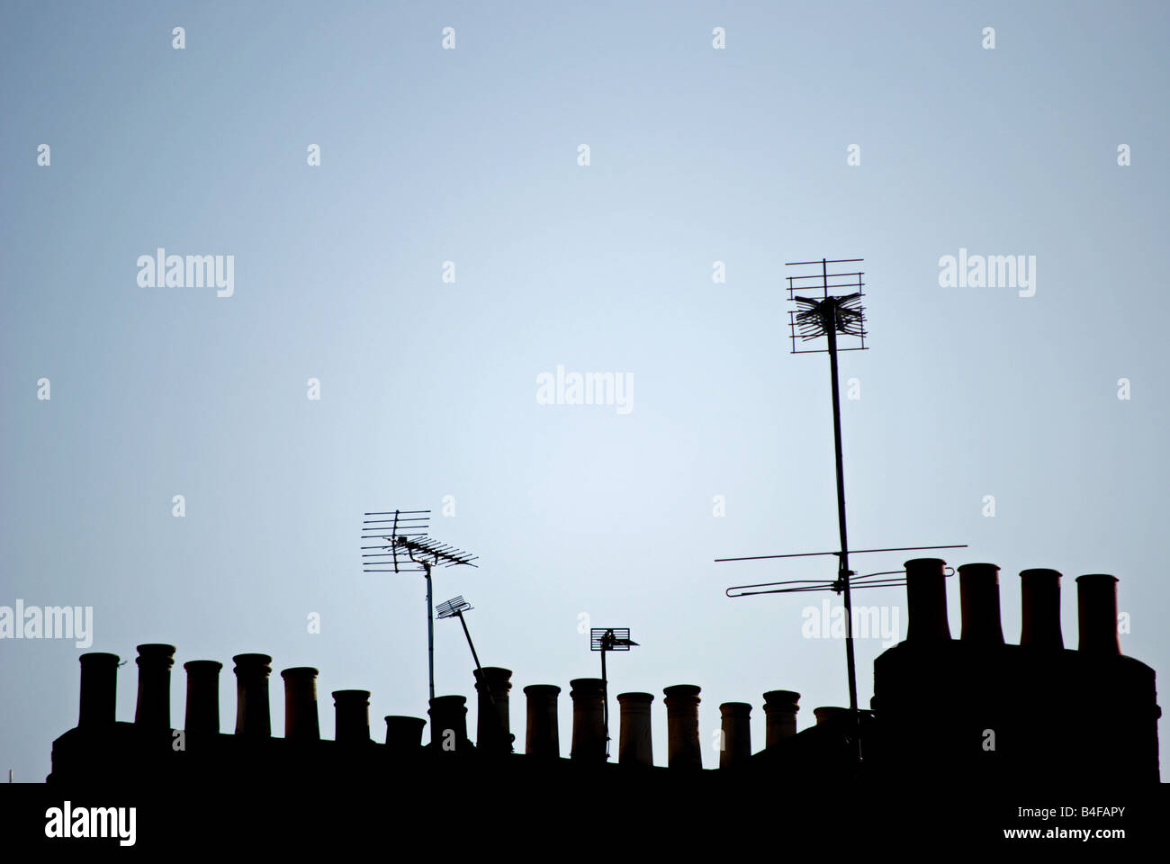 tv aerials and chimney pots seen in silhouette against an early morning blue sky, in twickenham, southwest london, - Stock Image