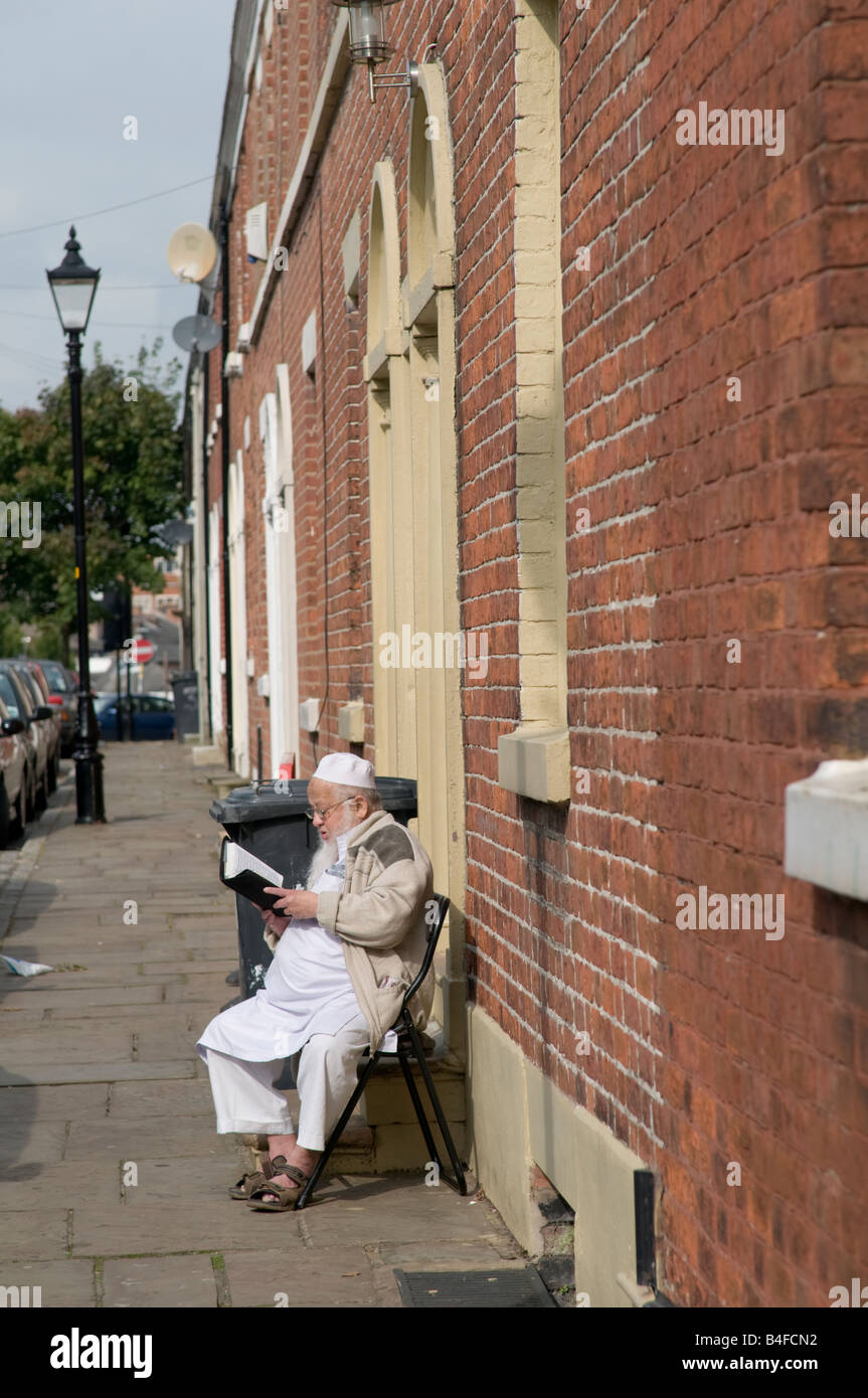 Elderly Moslem man reading religious book sitting on chair outside his terraced home in Preston Lancashire England - Stock Image