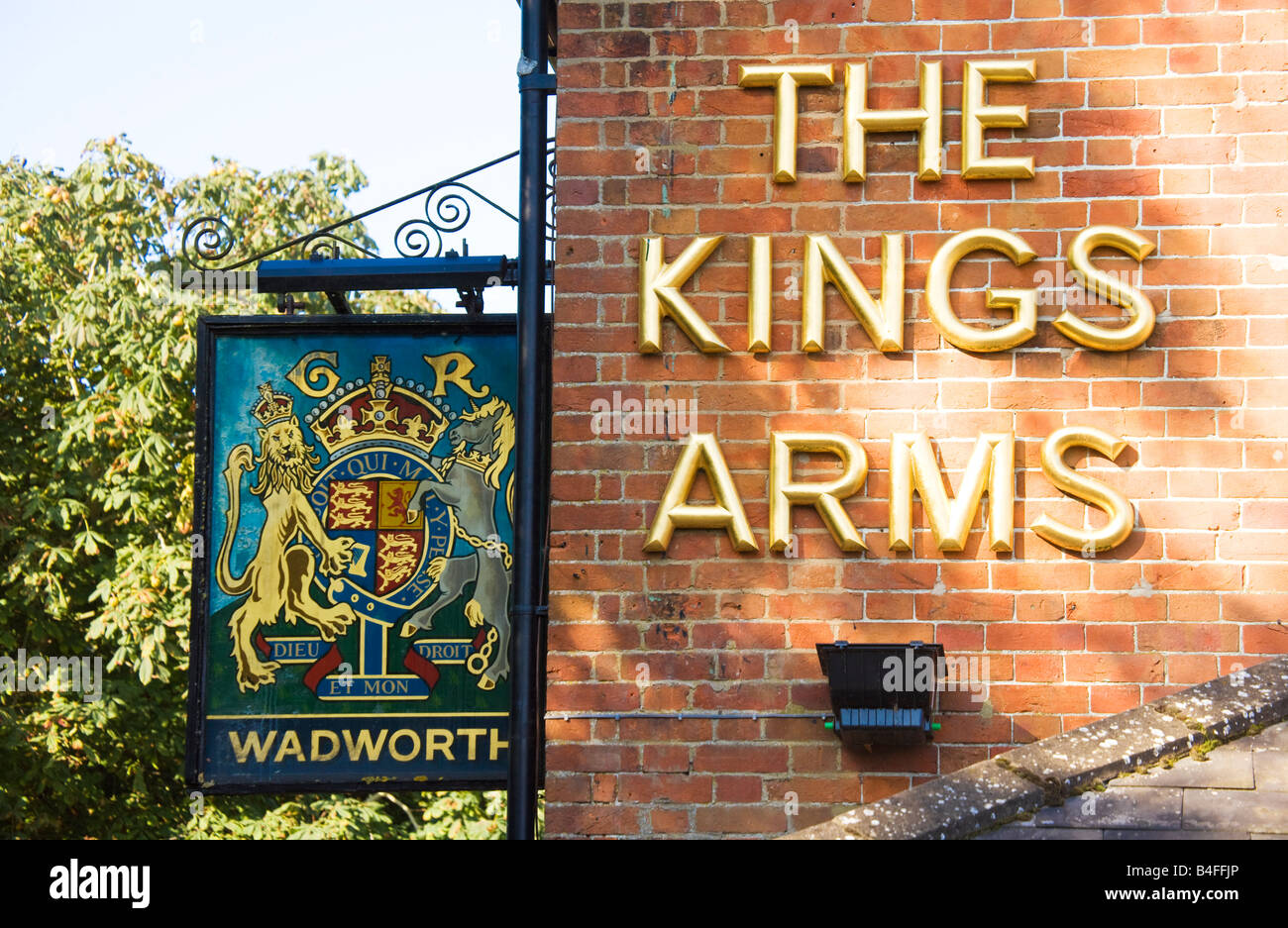 Hanging pub sign and gold letters on the wall of the King's Arms in All Cannings, Wiltshire, England, Great - Stock Image