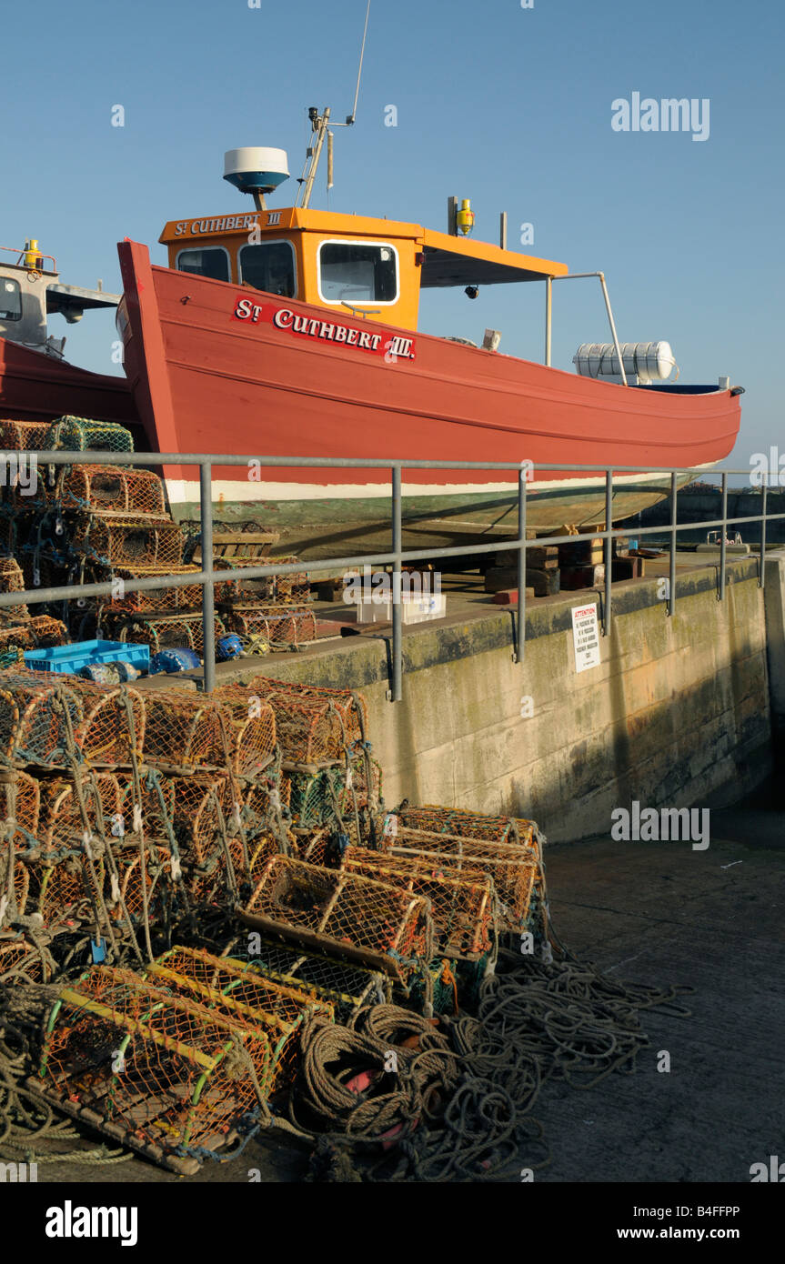Fishing boat,  lobster pots and crab pots on the quayside at Seahouses, Northumberland, England - Stock Image
