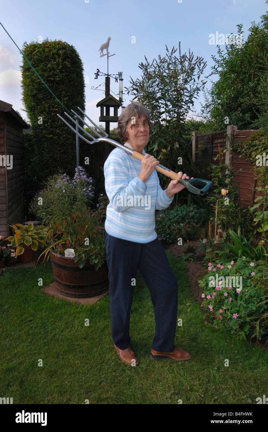 A Woman In Her Seventies Posing With A Garden Spade - Stock Image