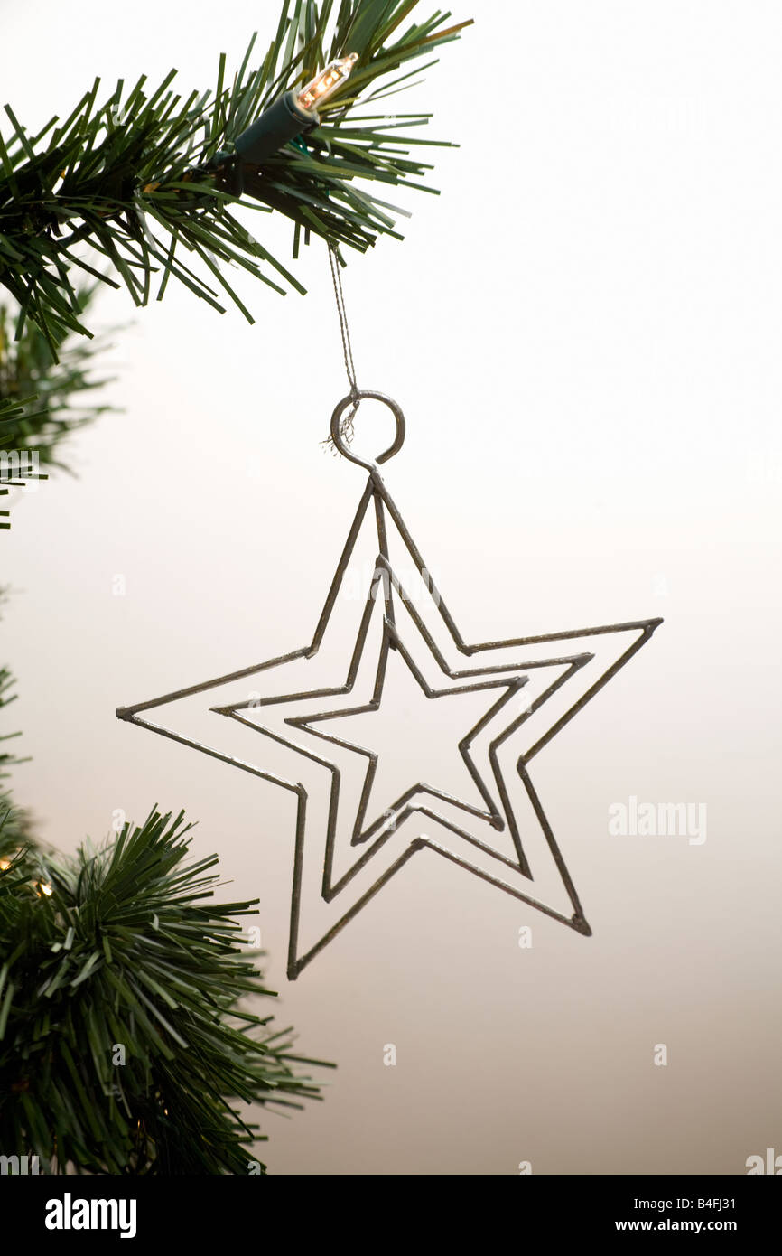 A Xmas star ornament hanging from the tree Stock Photo