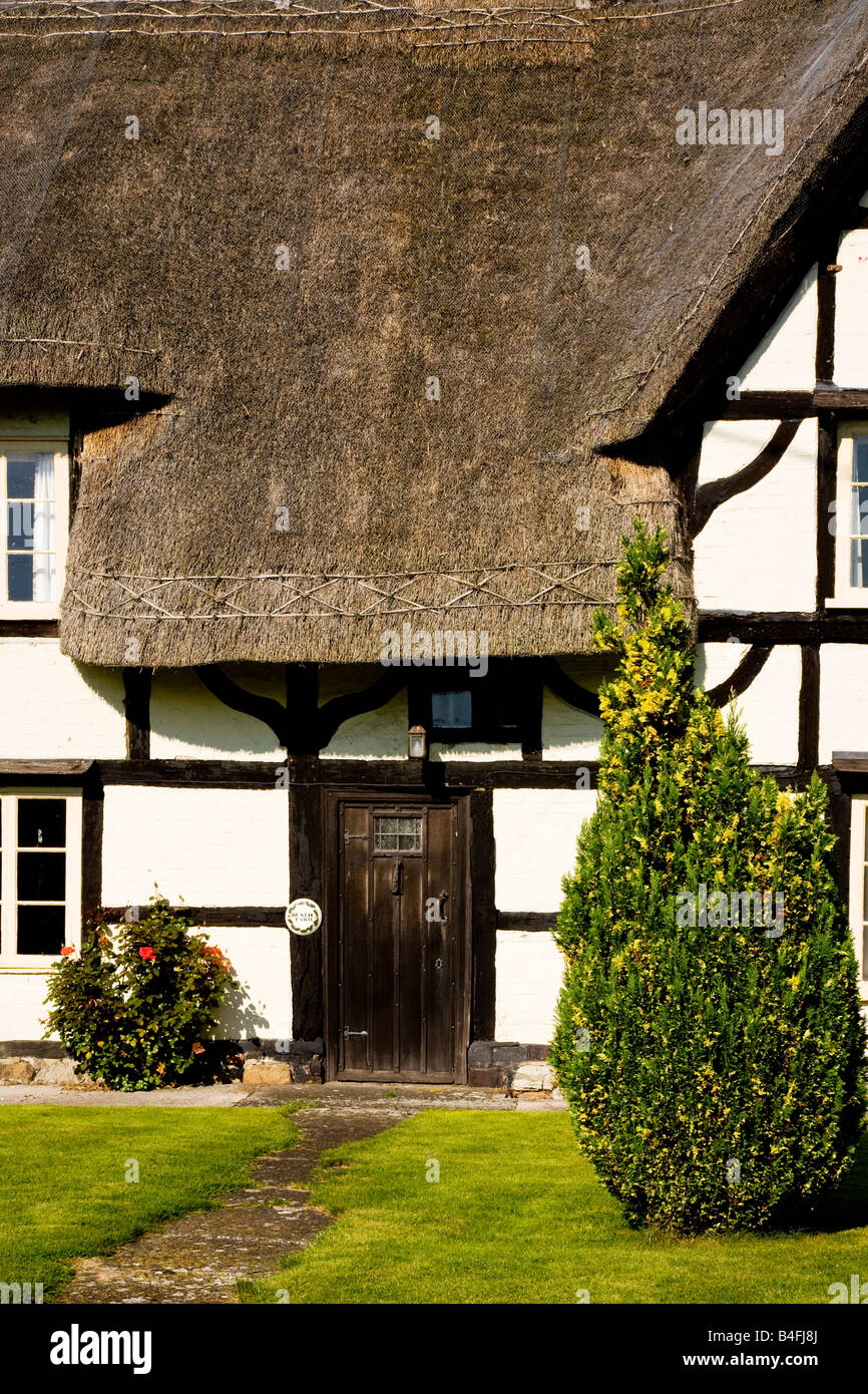 Close-up of the front of a typical English thatched country cottage in the village of All Cannings, Wiltshire, England, - Stock Image