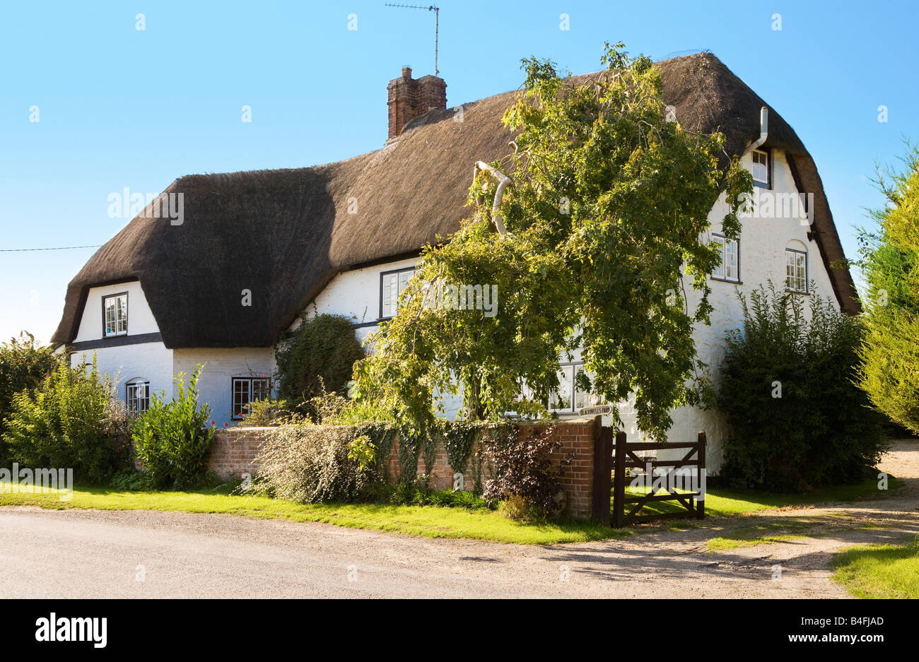 Typical English thatched country cottage in the village of Bishops Canning, Wiltshire, England, Great Britain, UK - Stock Image