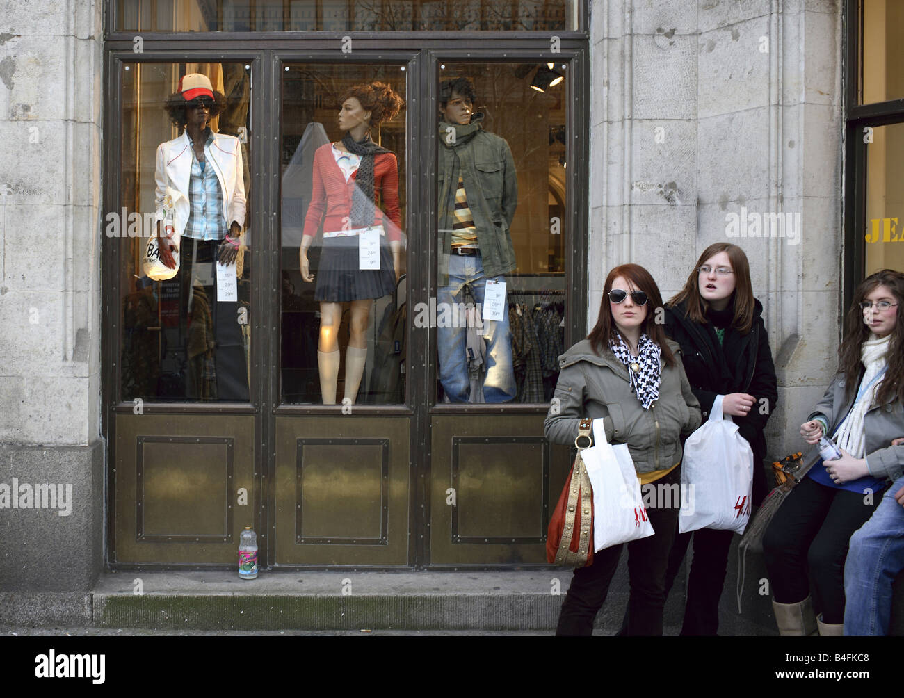 Girls in front of a shop window of H&M at the Kurfuerstendamm, Berlin, Germany - Stock Image