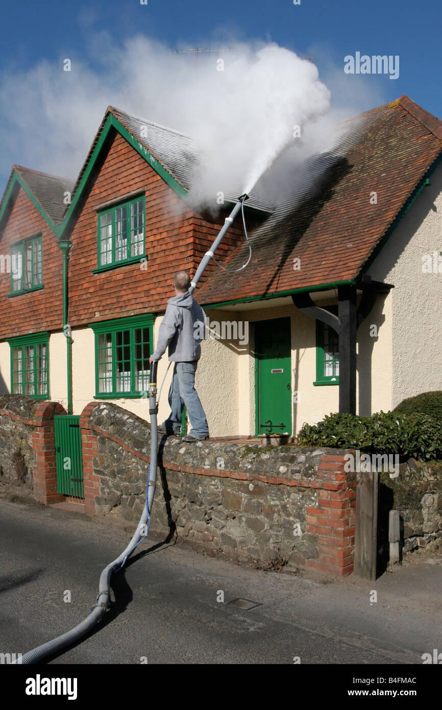 Blowing fake snow onto a cottage roof in the village of Shere, Surrey, for the film 'The Holiday' 2006 Stock Photo