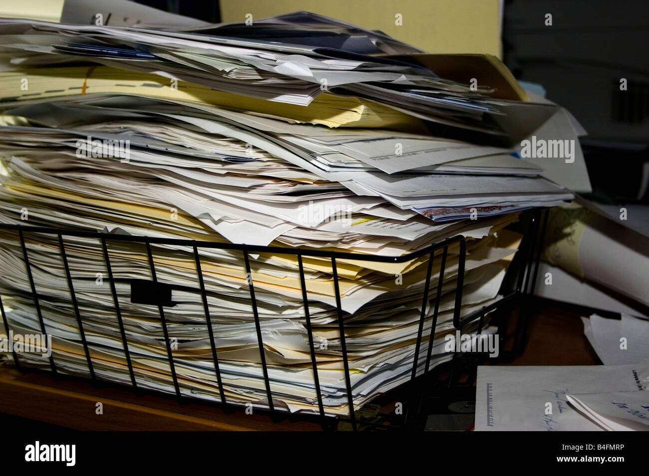A pile of papers and file folders stacked to overflowing in a black wire basket. - Stock Image