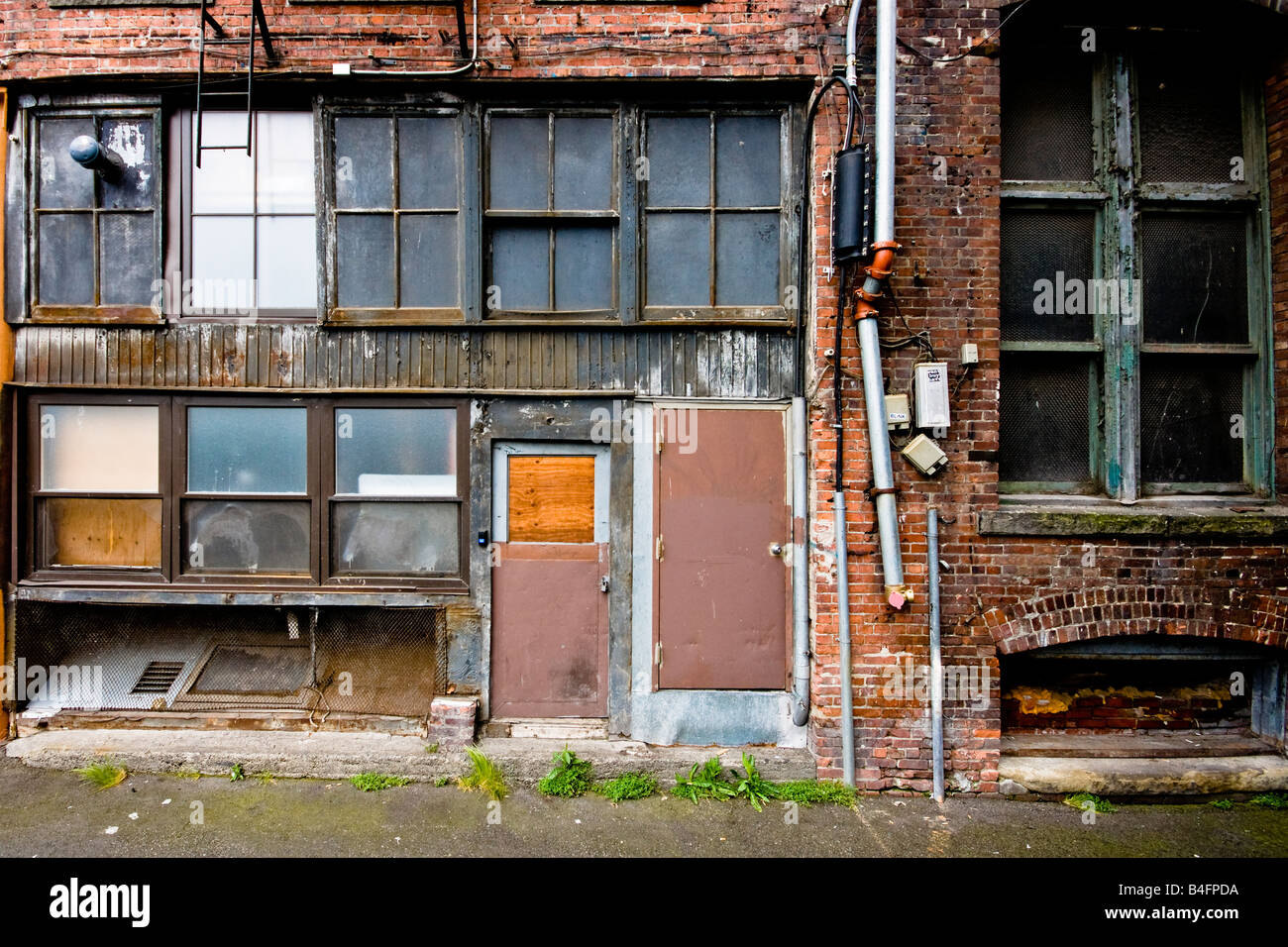 A beaten up entrance into the back of a factory in a brick wall in downtown Seattle, Washington. - Stock Image