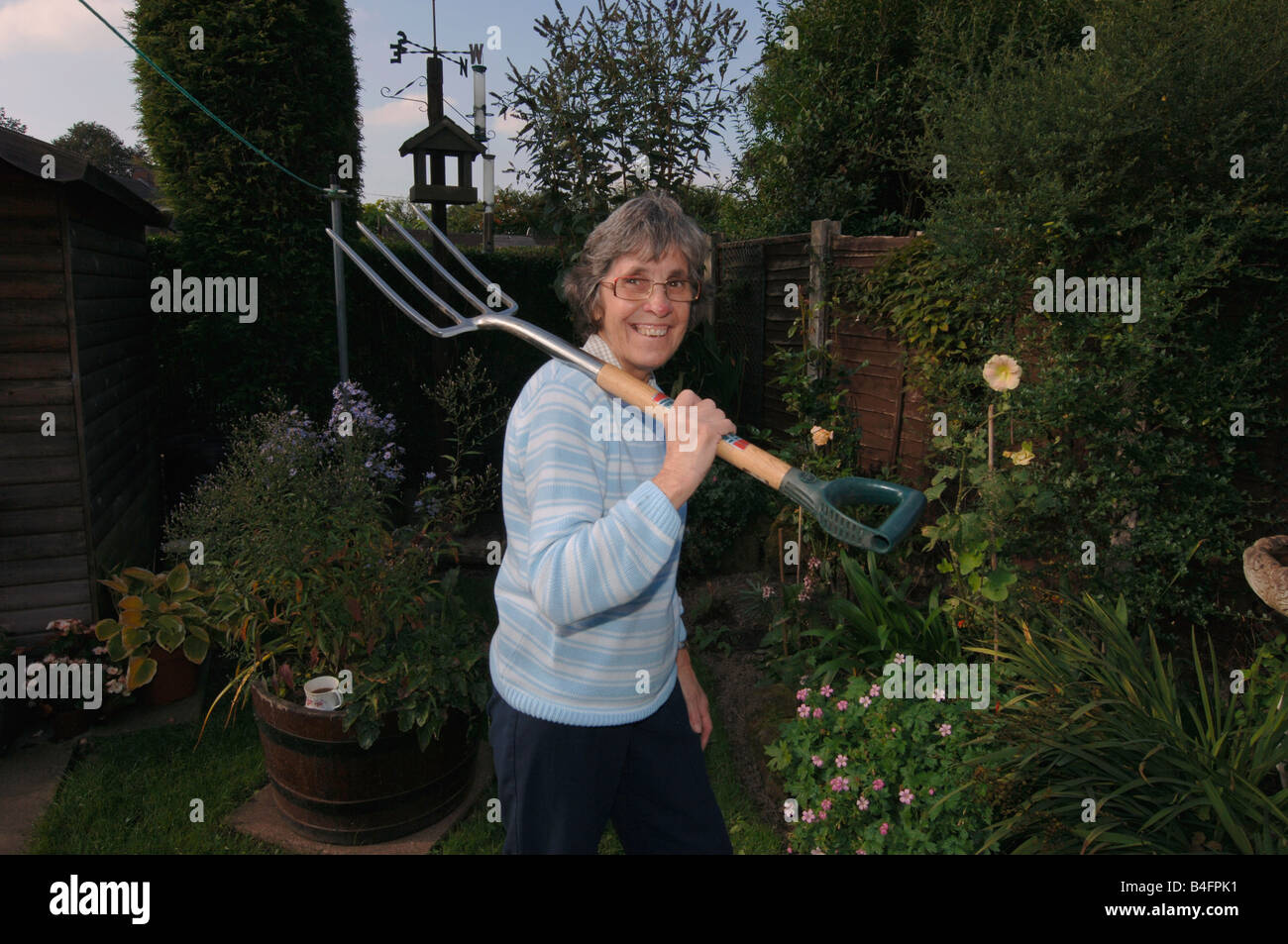 A Woman In Her Seventies Posing With A Garden Fork - Stock Image