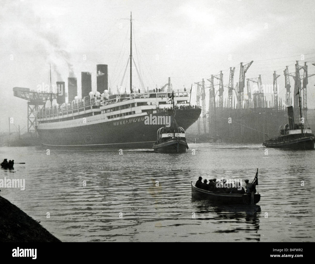 RMS Aquitania seen here being towed away from the John Brown shipyard on the River Clyde in Scotland circa 1913 - Stock Image