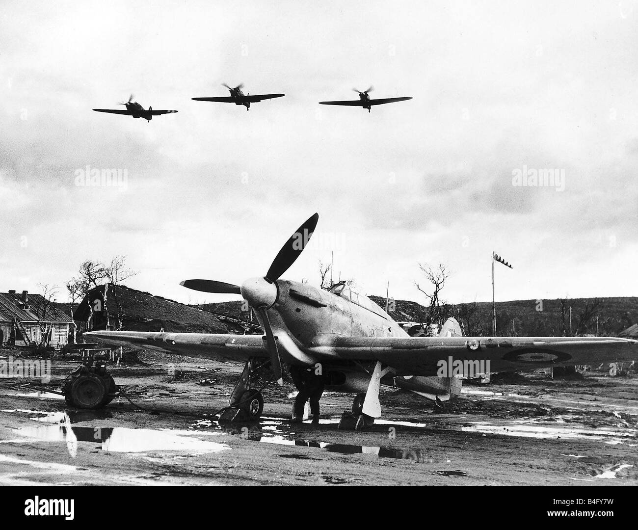 An RAF Hawker Hurricane sits on a muddy Russian airfield as Hurricanes fly overhead WW2 1941 - Stock Image