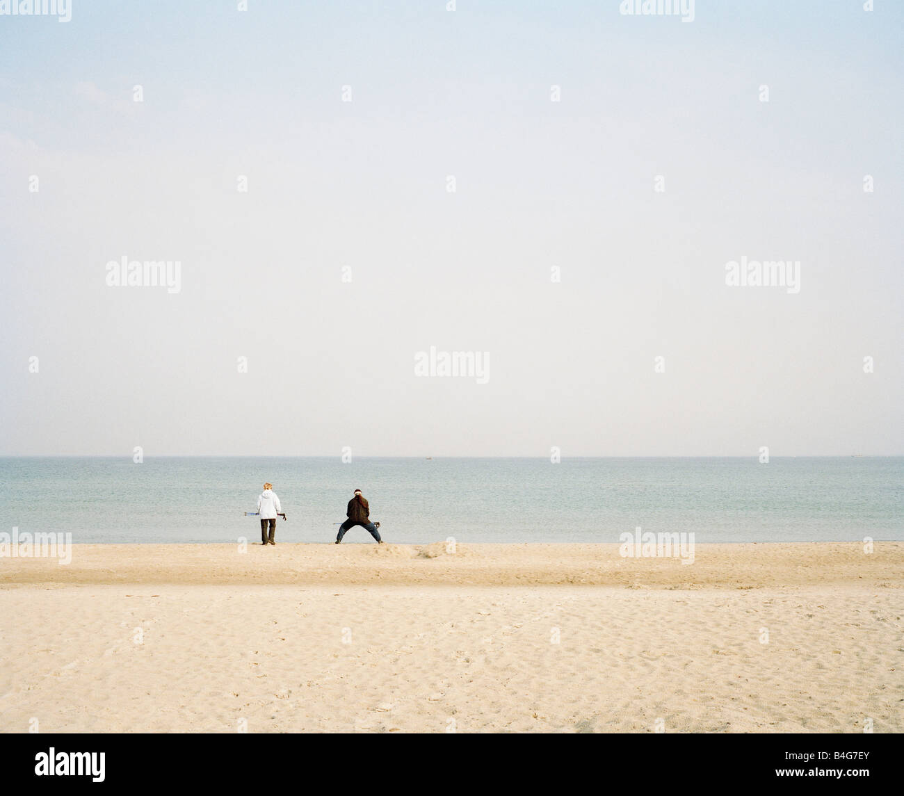 A beach at the Baltic Sea [Germany] with two unrecognizable people in the distance - Stock Image