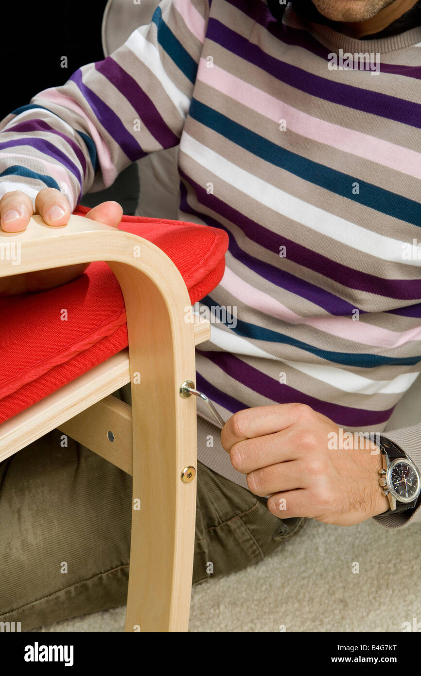 A man using a Allen wrench to tightening a screw on a chair - Stock Image