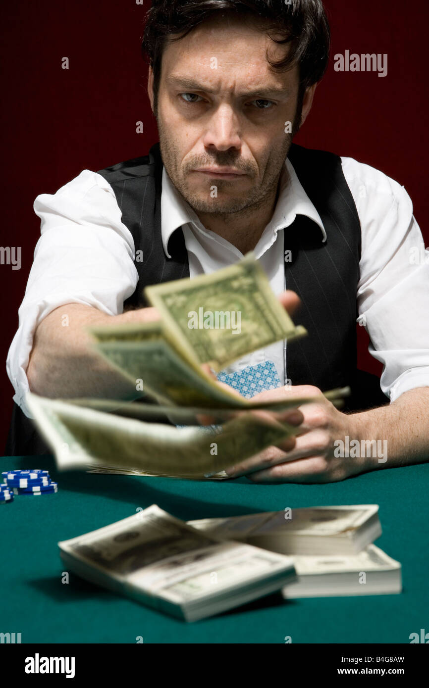 A man throwing money into the pot at a high stakes poker game - Stock Image