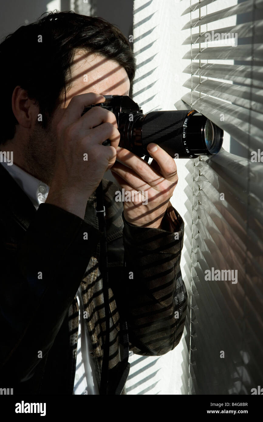 A man looking through blinds with a camera - Stock Image