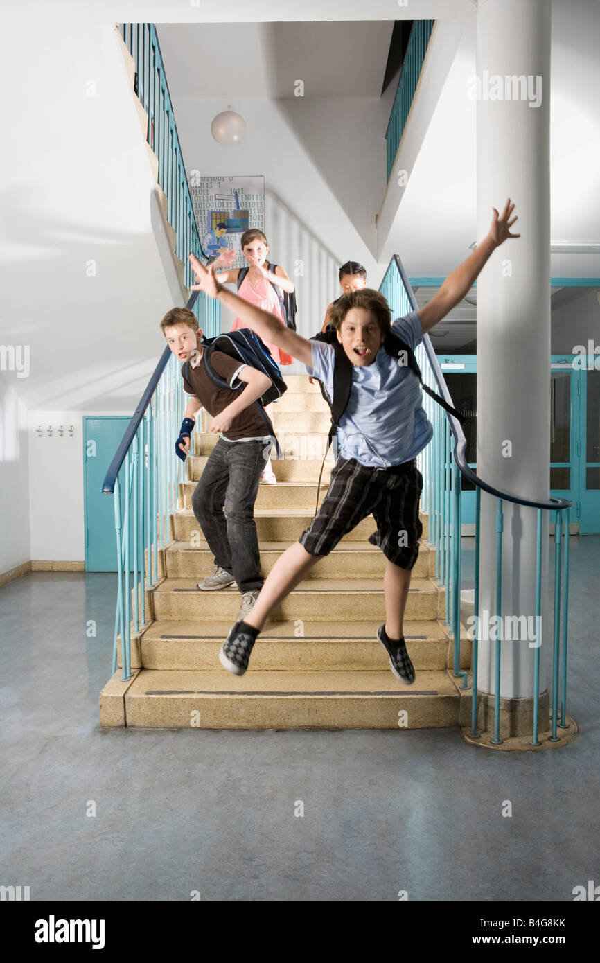 Four pre-adolescent children running down stairs excited - Stock Image