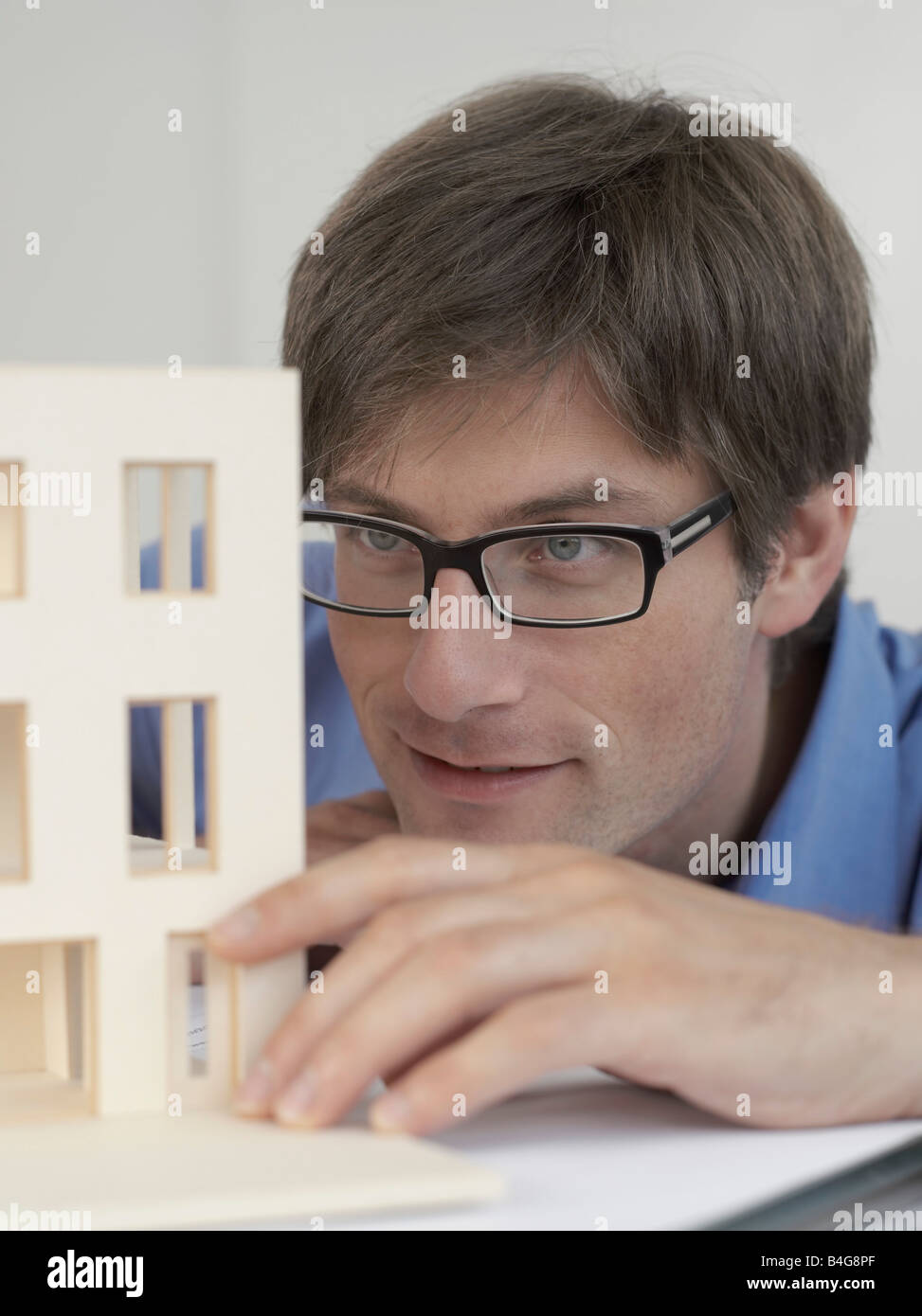 An architect examining an architectural model - Stock Image