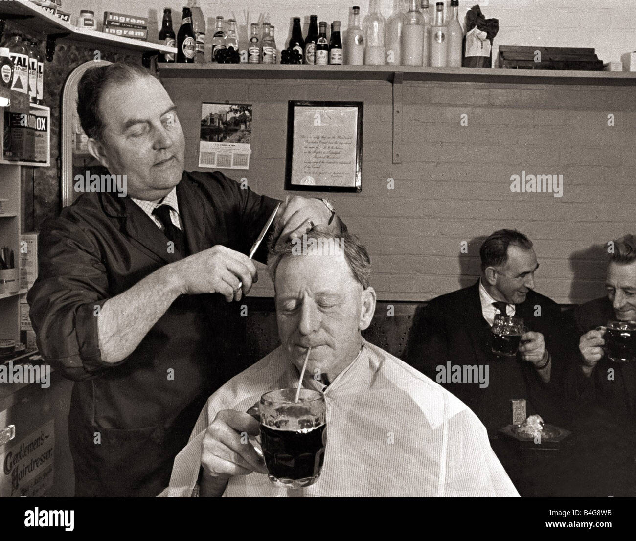 The landlord of the Railway Inn Bernard Fabian cuts hair in between pulling pints in the little shop attached to - Stock Image