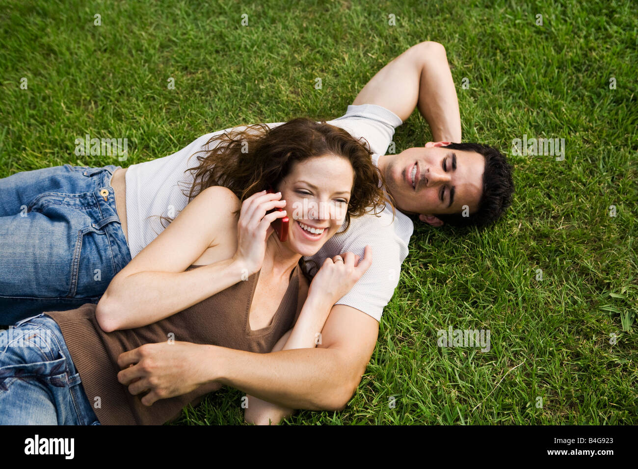 A young couple snuggling on a lawn Stock Photo