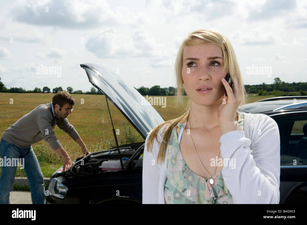 A couple standing at the roadside next to their broken down car - Stock Image