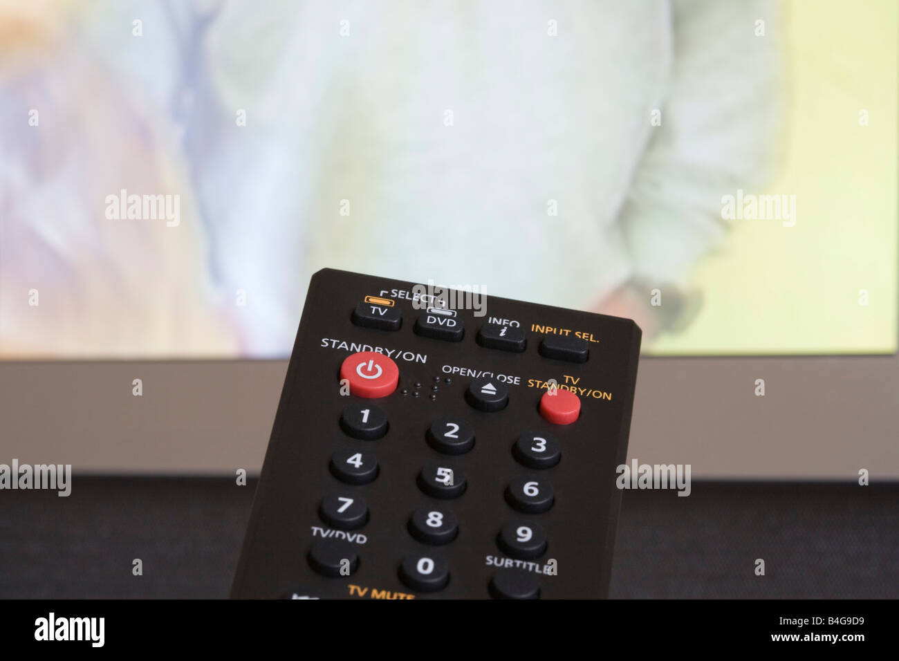 TV remote control with red standby button and television screen transmitting behind - Stock Image