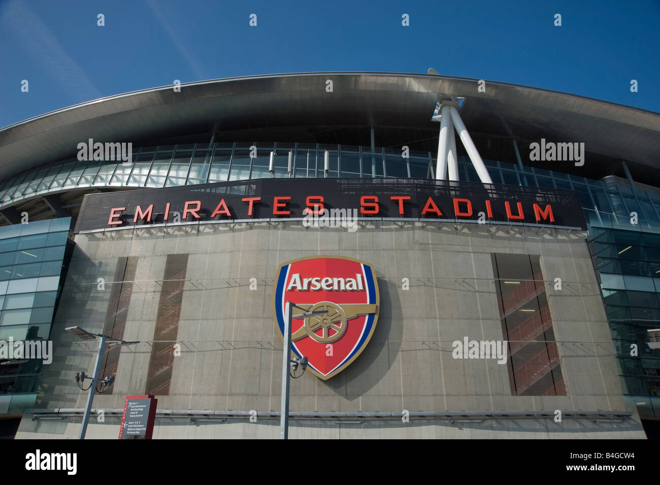 A view outside of the Arsenal Emirates stadium clearly showing the Emblem and Arsenal logo against a clear blue - Stock Image