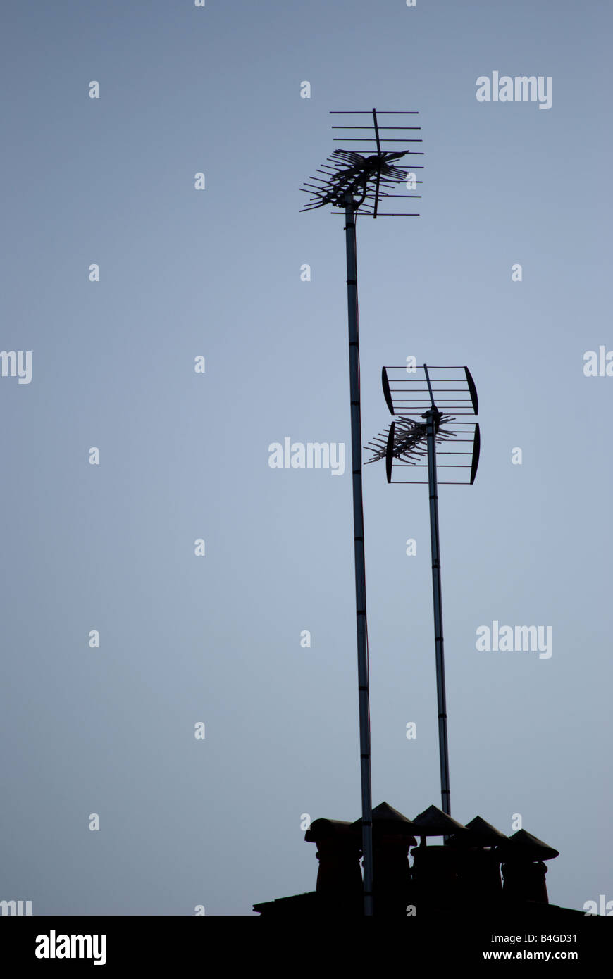 two tv aerials and chimney pots seen in silhouette against an early morning blue sky, in twickenham, southwest london, - Stock Image