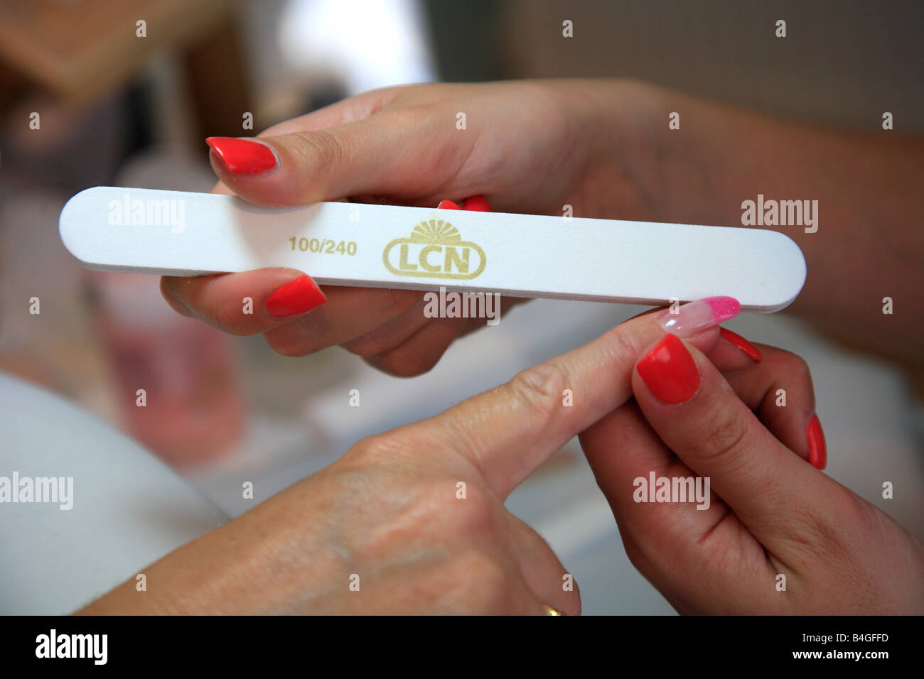 Manicure filing a Ladys Nails with a Nailfile in a Trendy High ...