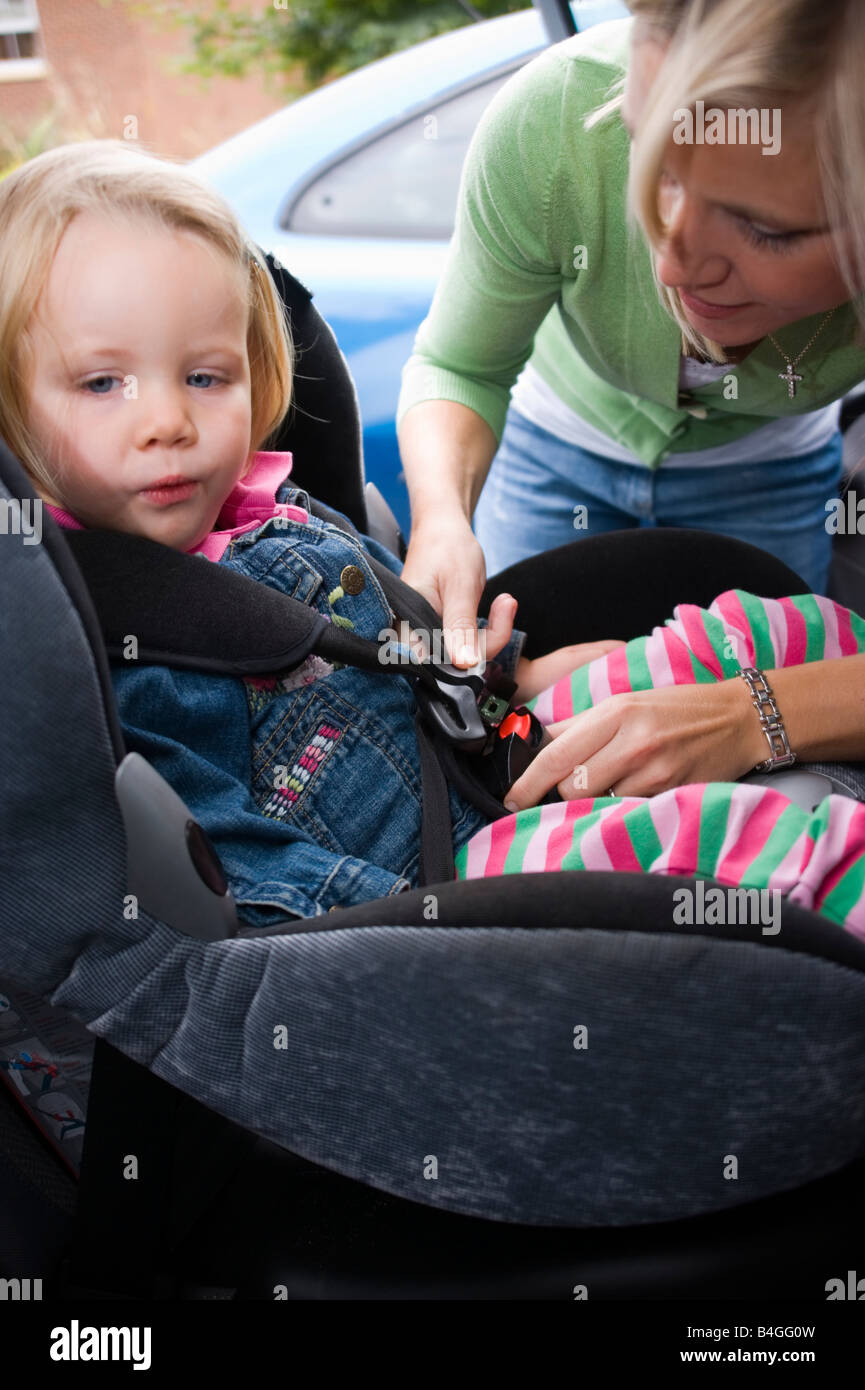 little girl being strapped into her car seat by her mother Stock ...