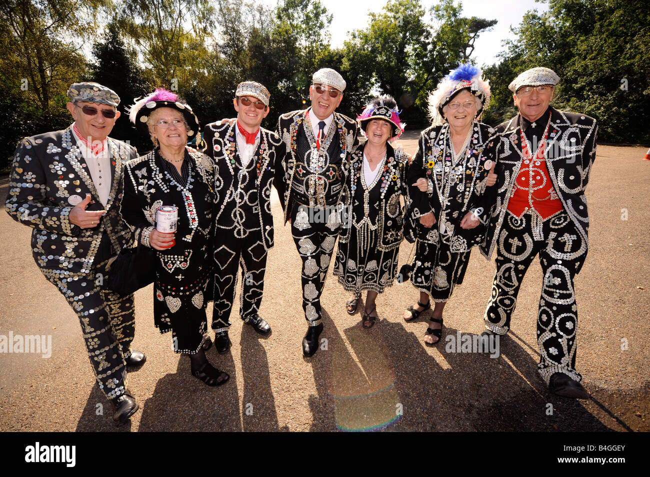 A group of London Pearly Kings & Queens linked arm in arm wearing their distinctive pearly suits. Picture by - Stock Image