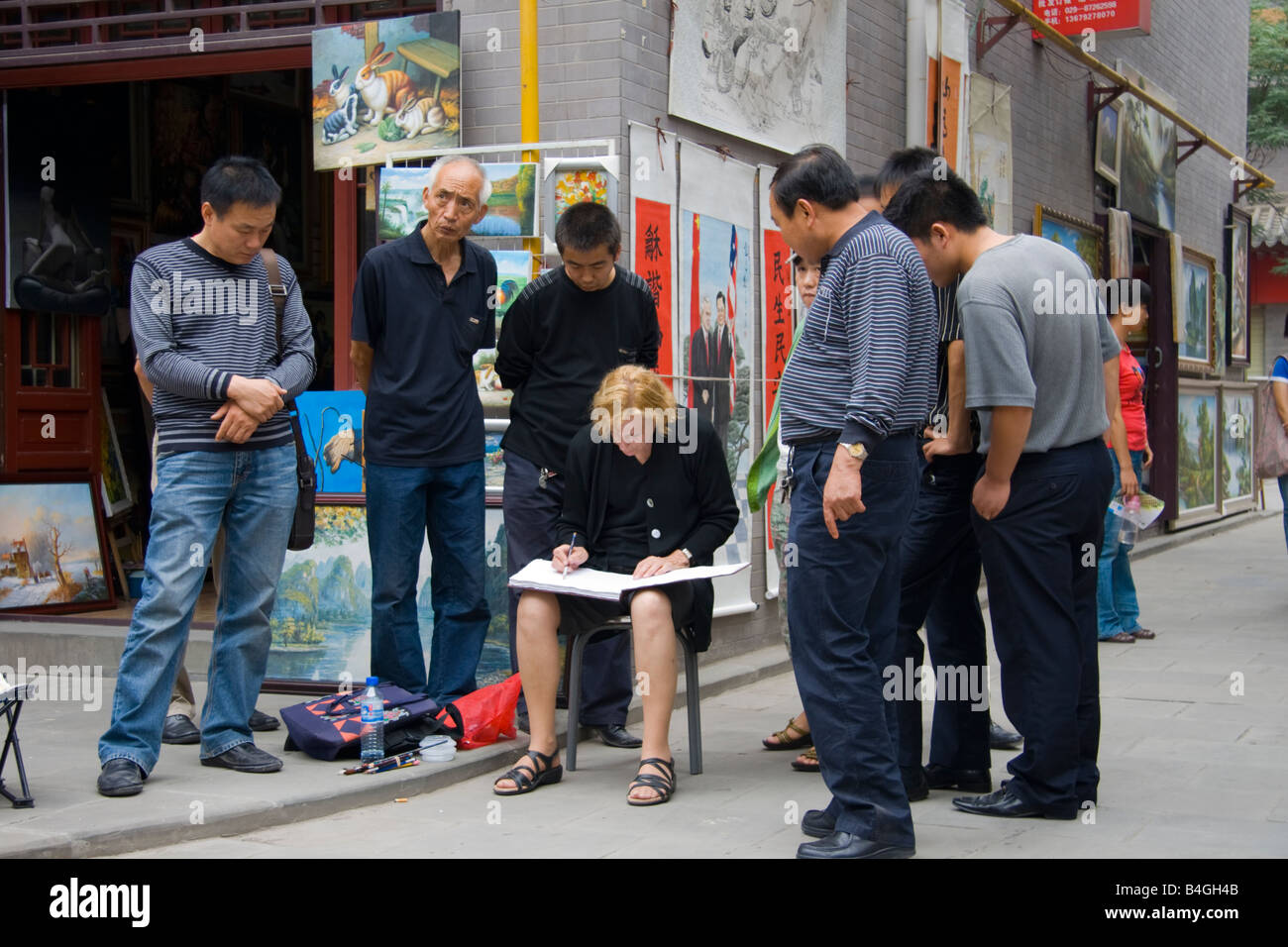 Onlookers watch a street artist in Xian , China - Stock Image